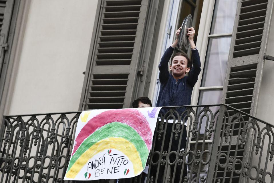 """bambino suona le pentole su un balcone su cui è appoggiato un cartello con la scritta """"andrà tutto bene"""""""