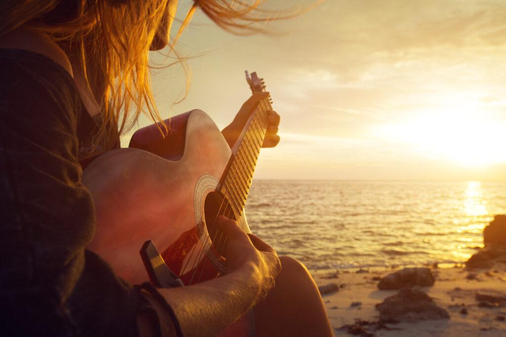 ragazza che suona la chitarra in spiaggia durante il tramonto