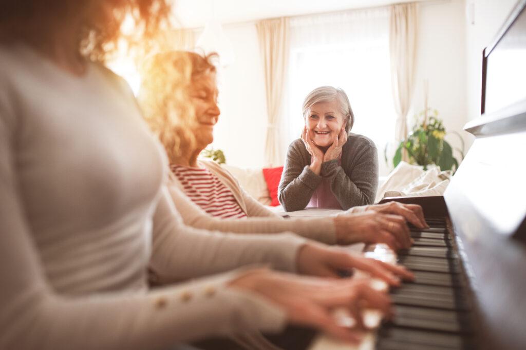 ragazza che suona il piano con la madre mentre la nonna le ascolta
