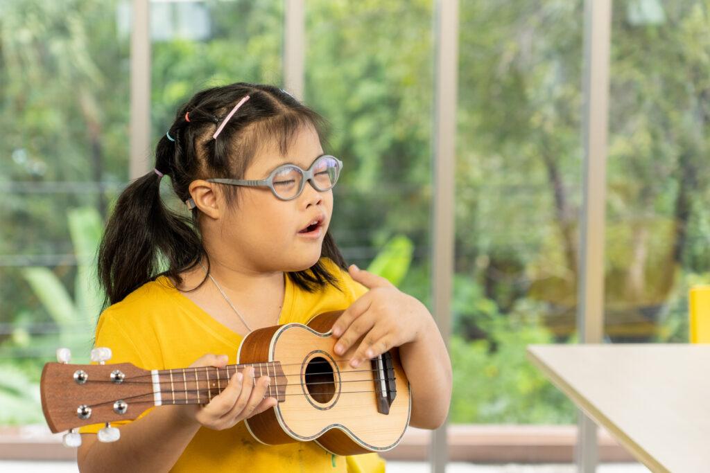bambina affetta da autismo che suona l'ukulele