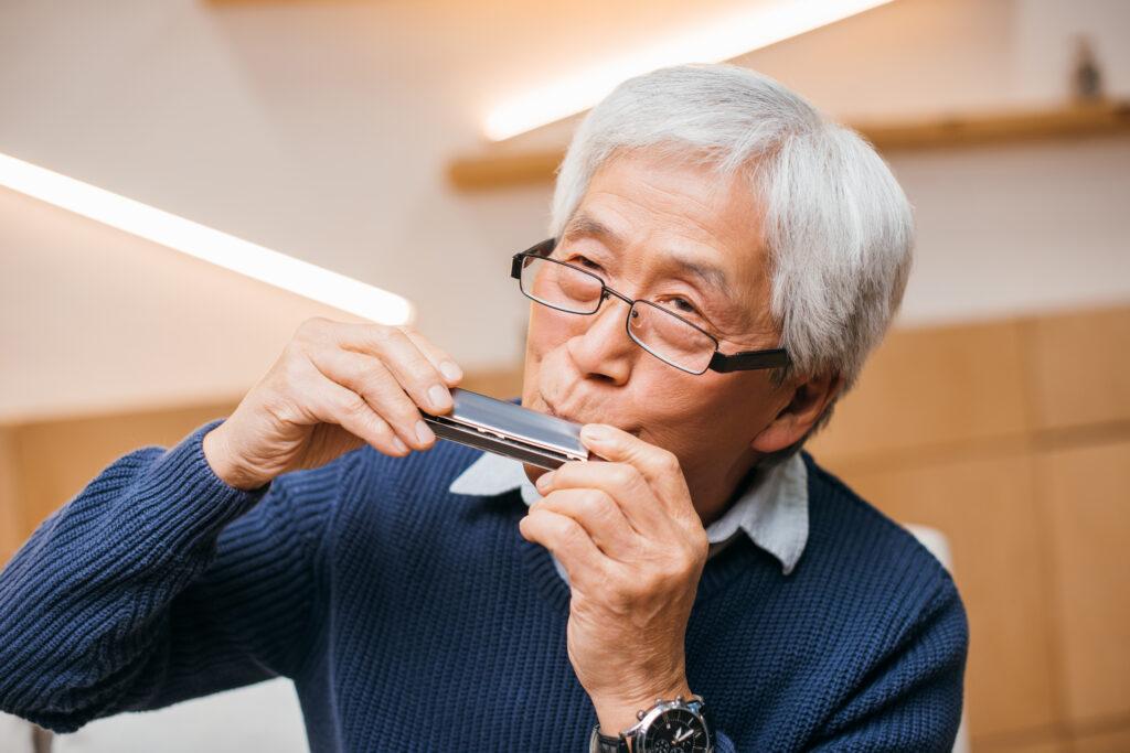 anziano che suona l'armonica