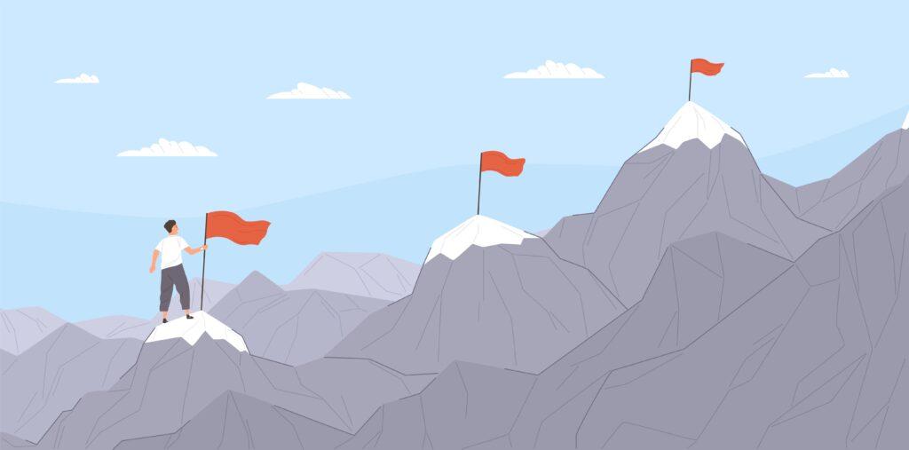 uomo che scala le montagne per arrivare in cima all'obiettivo