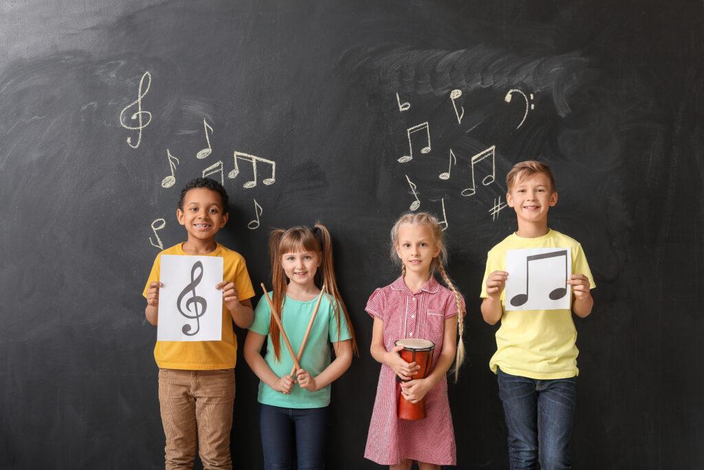 studenti con strumenti musicali in mano in piedi davanti a una lavagna